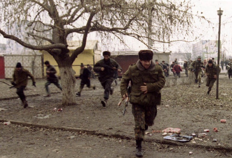 Chechen fighters run to take cover as they hear fighter jets flying overhead during an artillery and rocket attack in the centre of the Chechen capital - January 9, 1995. [Yannis Behrakis/Reuters]