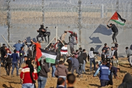 Palestinians rally with Palestinian flags as they try to climb the barbed wire fence east of Gaza City [Said Khatib/AFP]