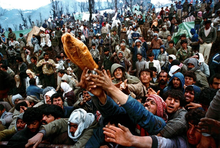 Frantic Kurdish refugees struggle for a loaf of bread during a humanitarian aid distribution at the Iraqi-Turkish border - April 5, 1991. [Yannis Behrakis/Reuters]