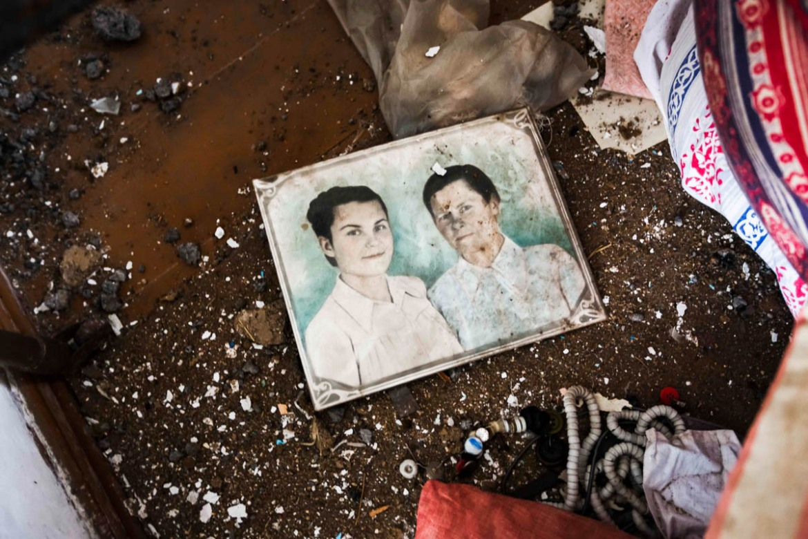 Family photos scattered on the floor of a shelled house in Shirokino, in Ukrainian territory. [Erik Messori/CAPTA/Al Jazeera]