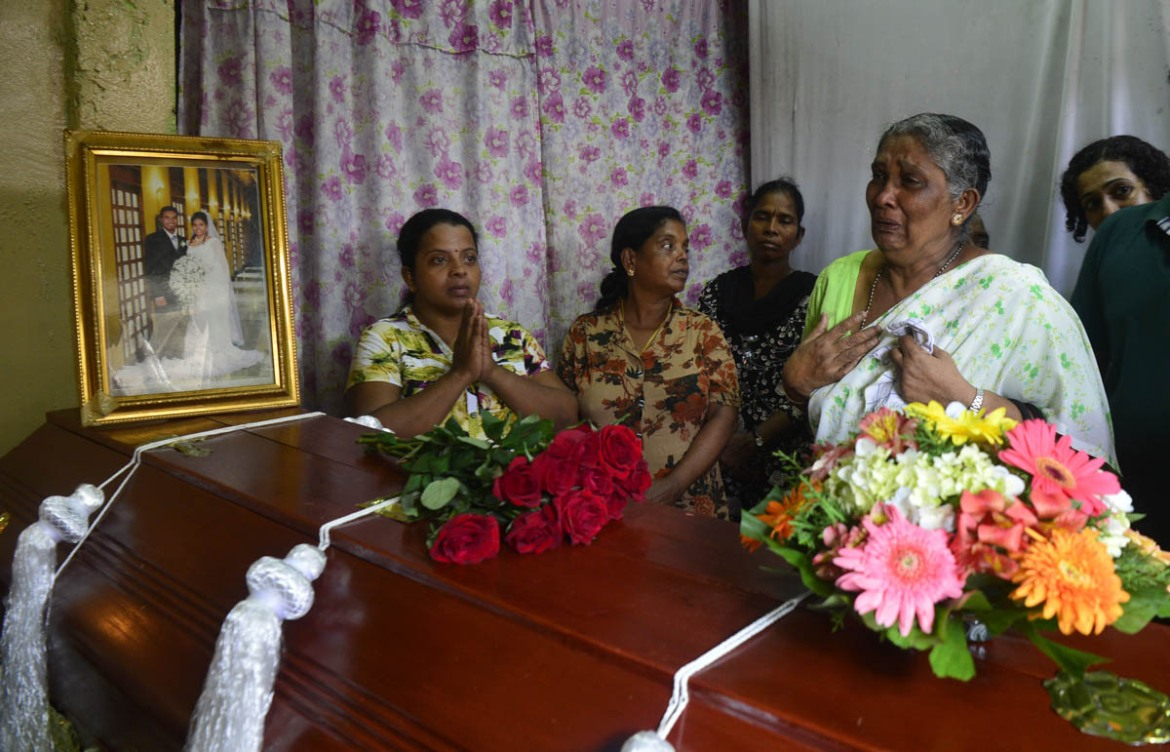 A Sri Lankan woman cries next to the coffin of a relative who died in an explosion at St Anthony's Shrine on Easter Sunday. [Lakruwan Wanniarachchi/AFP]