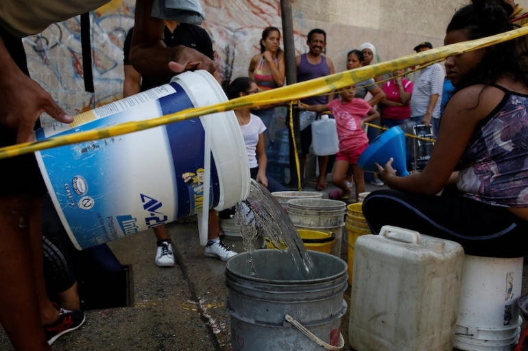 Locals line up to collect water from an underground water pipeline in Caracas [Carlos Garcia Rawlins/Reuters]
