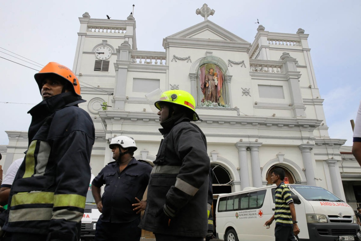 Sri Lankan firefighters in the area around St Anthony's Shrine after the blast in Colombo. [Eranga Jayawardena/AP]