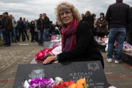 Shemsie Hoxha, 60, touches the grave of her son Ardian who was 14 when he was taken by Serb forces on April 17, 1999 and killed. 