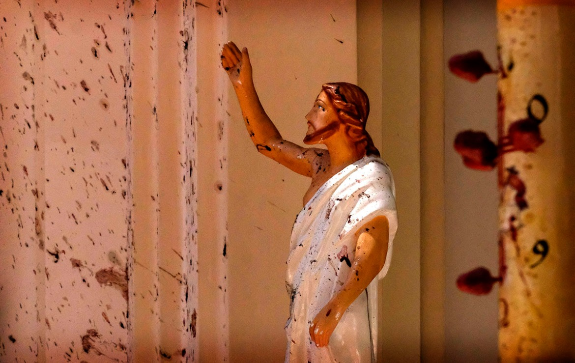 Blood stains are seen on a wall and on a Jesus Christ statue at the St. Sebastian's Church after blast in Negombo, north of Colombo. [AP Photo]