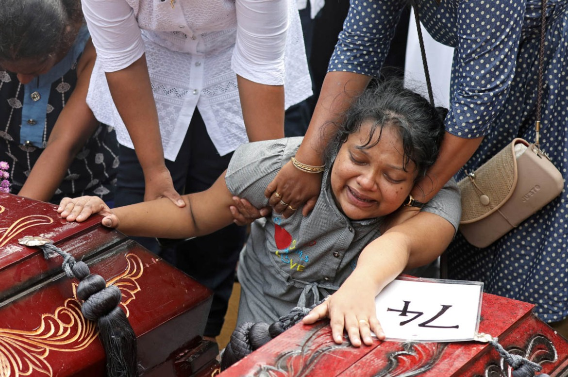 A woman collapses next to two coffins during a mass burial of victims, two days after a string of bomb attacks on churches and luxury hotels across Sri Lanka on Easter Sunday killed more than 320 people. [Athit Perawongmetha/Reuters]