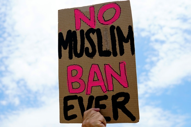 A protester holds up a sign that reads 'No Muslim Ban Ever' as he protests against the Supreme Court ruling upholding US President Donald Trump's travel ban outside the the Supreme Court in Washington, DC in 2018 [File: Carolyn Kaster/AP Photo]