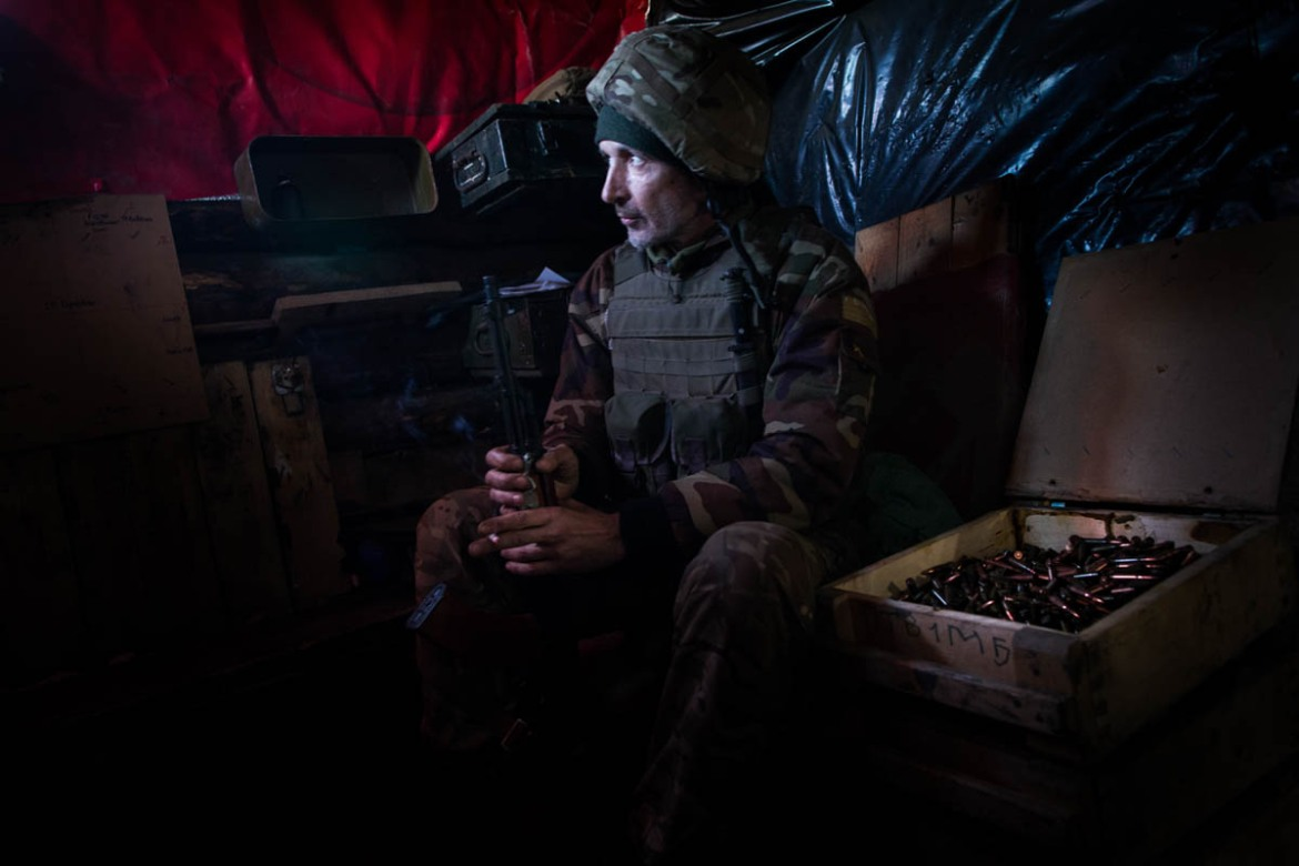 Levit, a 50-year-old Ukrainian soldier, part of the 92nd Battalion, smokes a cigarette in the lookout post, located in Shakta Butovka, Avdiivka, just 200 metres from the separatists. [Erik Messori/CAPTA/Al Jazeera]