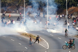 Tear gas was fired on a highway near the airbase where Guaido appeared with the military men [Carlos Garcia Rawlins/Reuters]