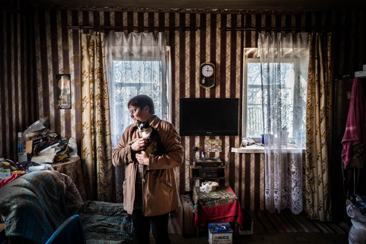 Natasha, 40 years-old, looks for some conserves in the bunker of her house located in Zaitseve, just a few hundred metres from the front line. [Erik Messori/CAPTA/Al Jazeera]