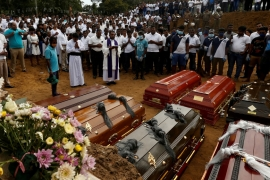 People participate in a mass funeral, of the seven victims belonging to one family, in Negombo [Thomas Peter/Reuters]