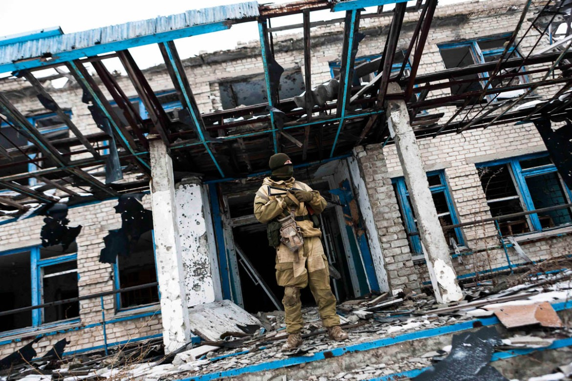A Ukrainian soldier in front of a destroyed school in Chernenko, Mariupol, after a heavy firefight. [Erik Messori/CAPTA/Al Jazeera]