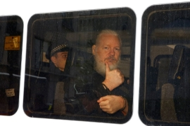 WikiLeaks founder Julian Assange is seen in a police van after he was arrested by British police outside the Ecuadorian embassy in London, on April 11, 2019 [File: Reuters/Henry Nicholls]
