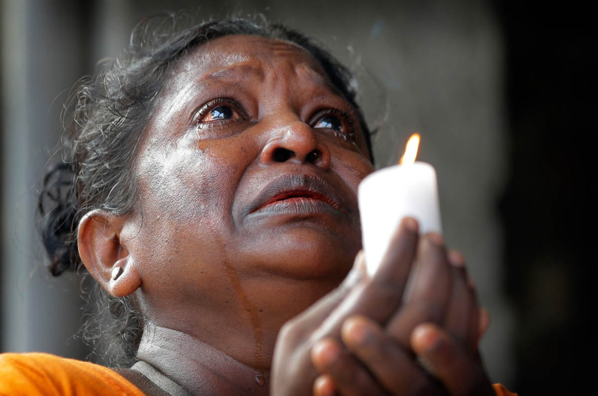 A Sri Lankan woman prays during a three-minute nationwide silence observed on Tuesday to pay homage to the victims of the Easter Sunday blasts. [Eranga Jayawardena/AP]