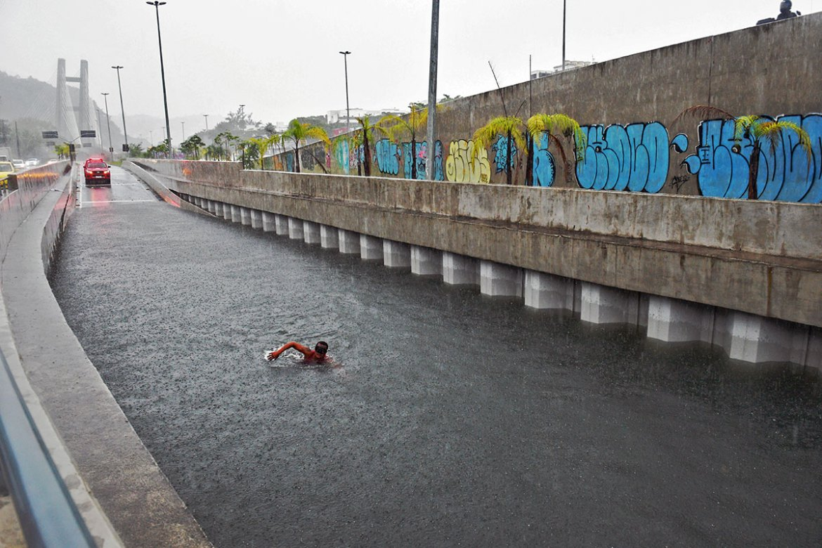Firefighters from the city's underwater unit dived into flooded tunnels to inspect submerged cars. [Carl de Souza/AFP]