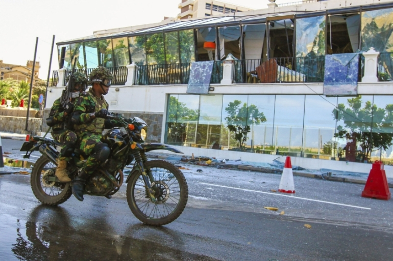 Soldiers on a motorcycle ride past the Kingsbury Hotel, which was attacked by a suicide bomber in Colombo [Chamila Karunarathne/AP Photo]