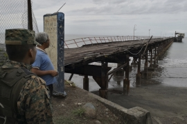 A police officer and a resident look at an abandoned pier in Puerto Armuelles after the quake made the structure at the end incline to the right [AP]