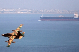 An Iranian military plane flies past an oil tanker during naval manoeuvres in the Gulf and Sea of Oman [File: Fars/via Reuters]