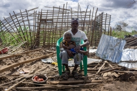 Louis Jose Batista sits with his son outside their home in Zone Seta, destroyed by Cyclone Kenneth [Tendai Marima/Al Jazeera]