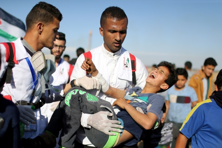 A wounded Palestinian boy is evacuated during a protest at the Israel-Gaza fence [Ibraheem Abu Mustafa/Reuters]