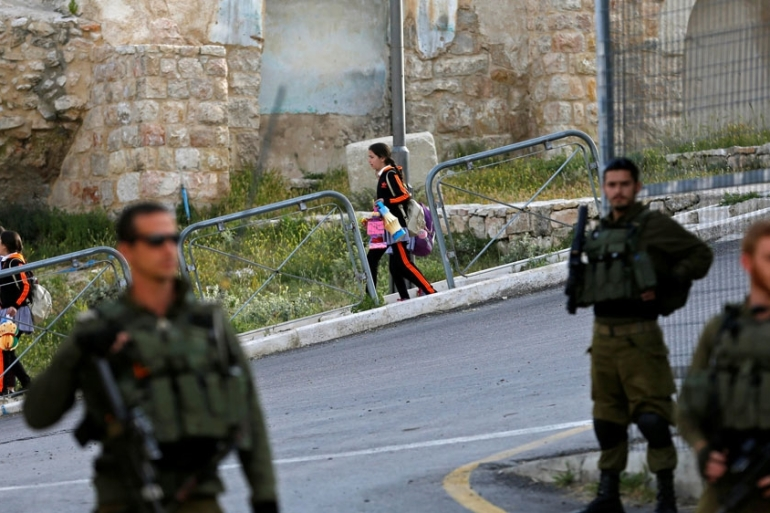 Palestinian schoolchildren make their way to school as Israeli soldiers stand guard, in Hebron, in the Israeli-occupied West Bank [Mussa Qawasma/Reuters file]
