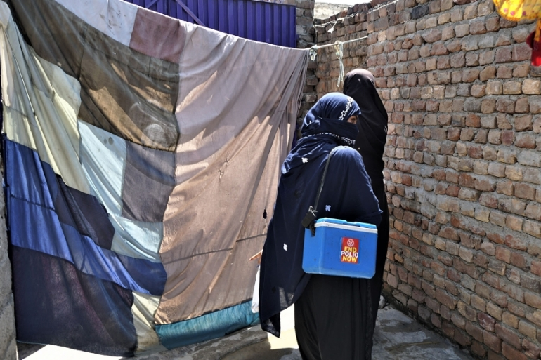 A pair of government-employed polio vaccinators in Nowshera knock on doors [Sabrina Toppa/Al Jazeera]