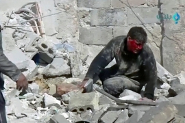 A wounded man sits in the rubble after an air attack in Khan Sheikhoun, Idlib province, in February [File: Reuters]