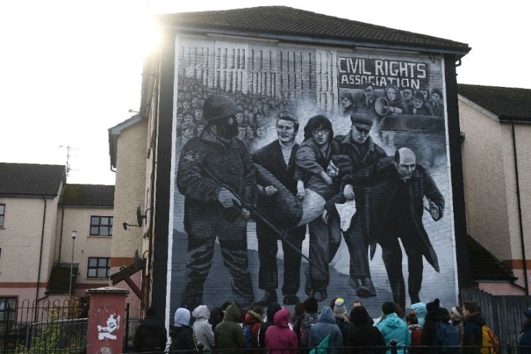 Tourists gather in front of a mural depicting the Bloody Sunday events in Londonderry [Clodagh Kilcoyne/Reuters]
