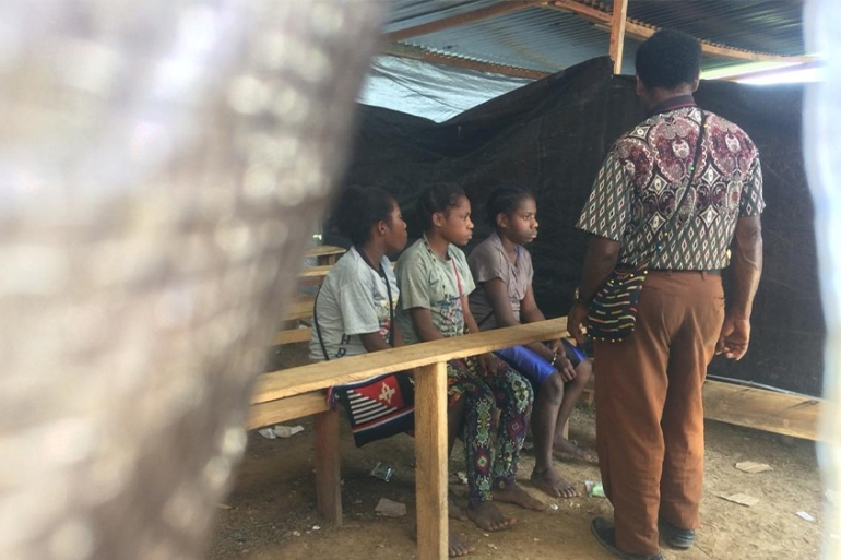 Children sit on benches at a temporary school built for those feeling unrest in Nduga [Febriana Firdaus/Al Jazeera]