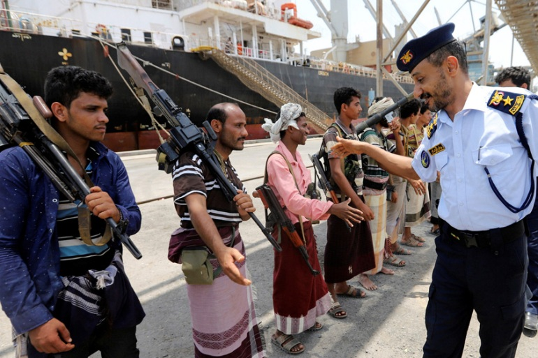 A Yemeni coastguard officer shakes hands with members of the Houthi movement as they withdraw from Saleef port [Abduljabbar Zeyad/Reuters]