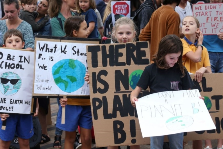 Schoolchildren hold handmade signs at a student-organised protest in Sydney on May 3 [Rick Rycroft/AP Photo]