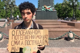 Arshak Makichyan holds a sign reading 'Our mass media is silent about global warming, but we are the ones who will suffer' [Jonathan Brown/Al Jazeera]