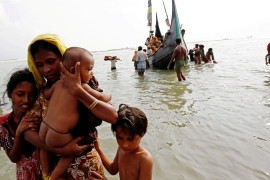 A Rohingya refugee and her children wade ashore after crossing the Bangladesh-Myanmar border by boat in September 2017 [File: Mohammad Ponir Hossain/Reuters]