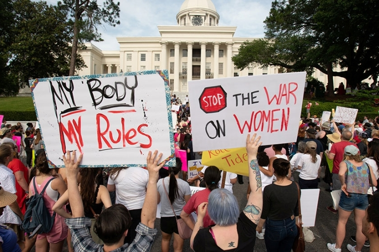 People gather at the Alabama State Capitol during the March for Reproductive Freedom against the state's new abortion law [File: Michael Spooneybarger/Reuters]