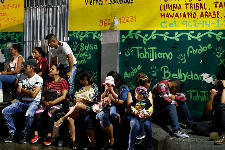 Migrants wait before dawn outside the offices of the Mexican Commission for Refugee Assistance, where hundreds a day are lining up to seek a legal document permitting them to stay in the country, in Tapachula, Mexico [Rebecca Blackwell/AP Photo]