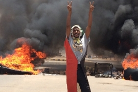 A protester flashes the victory sign in front of burning tires and debris on road 60 [AP Photo]