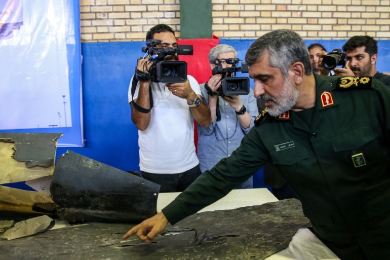 General Amir Ali Hajizadeh (right), commander of IRGC's aerospace division, speaks to media next to debris reportedly from a downed US drone recovered within Iran''s territorial waters [Meghdad Madadi/ Tasnim News/ AFP]