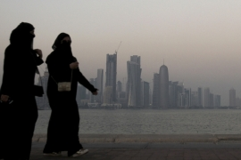 Women walk along the Corniche with downtown Doha in the background [File: Fadi al-Assaad/Reuters]
