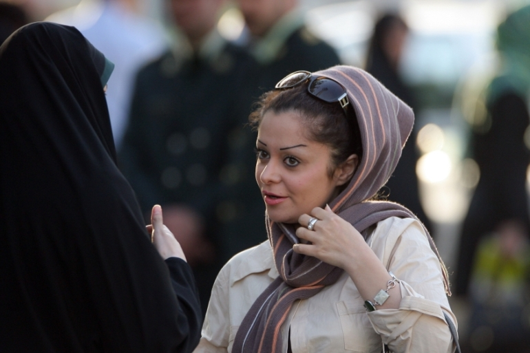 Iran's law requires women to cover their hair and wear loose garment to hide their body and skin [Majid Saeedi/Getty Images]
