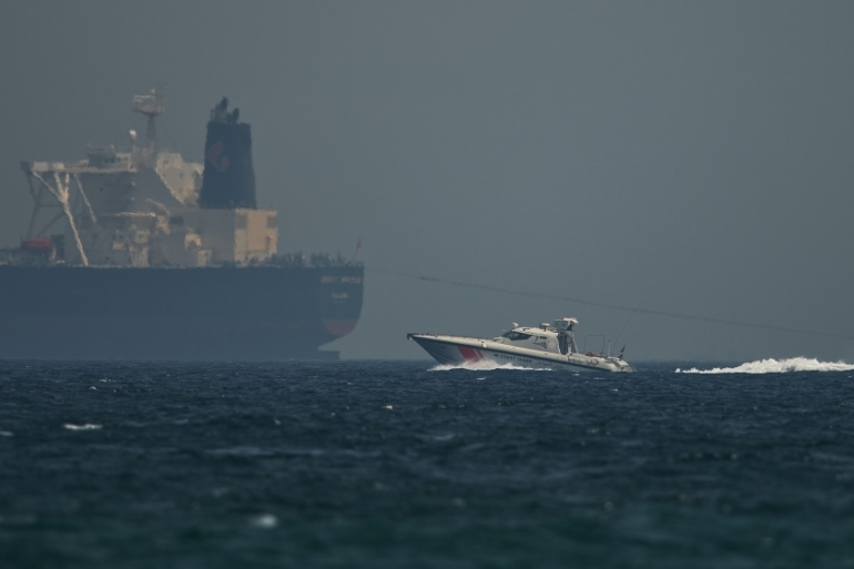 "An Emirati coast guard vessel passes an oil tanker off the coast of Fujairah, United Arab Emirates, Monday, May 13, 2019. Saudi Arabia said Monday two of its oil tankers were sabotaged off the coast of the United Arab Emirates near Fujairah in attacks that caused ""significant damage"" to the vessels, one of them as it was en route to pick up Saudi oil to take to the United States. (AP Photo/Jon Gambrell) [The Associated Press]"