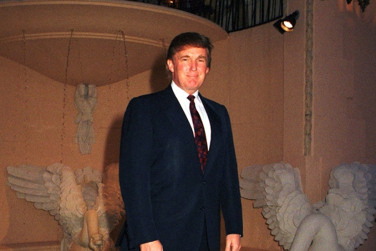 Trump poses in front of a swan fountain at the Mar-A-Lago estate, Palm Beach, Florida in 1996 [File: Getty Images]