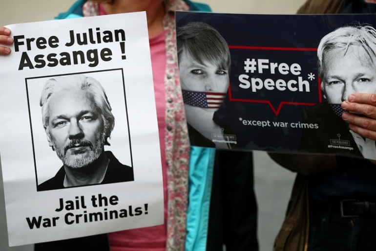 Protesters hold placards calling for Julian Assange's release outside of Westminster Magistrates Court in London, UK [File: Hannah Mckay/ Reuters]