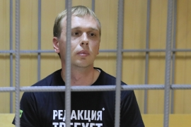 Russian investigative journalist Ivan Golunov, who was detained and accused of drug offences, sits inside a defendants' cage during a court hearing in Moscow on June 8 [Reuters/Tatyana Makeyeva]