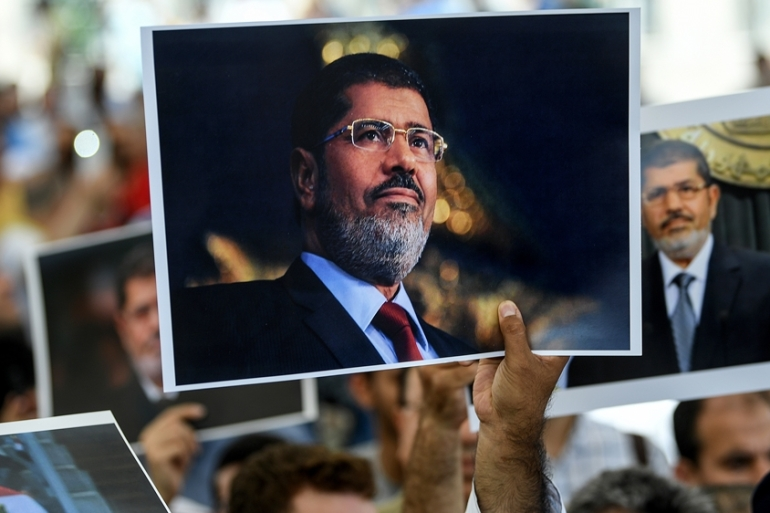 People hold picture of Egyptian President Mohamed Morsi during a symbolic funeral ceremony at Fatih mosque in Istanbul [AFP]