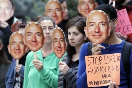 Demonstrators hold images of Amazon CEO Jeff Bezos during a protest over the company's facial recognition system at the Amazon headquarters in Seattle on October 31, 2018 [File: AP/Elaine Thompson]
