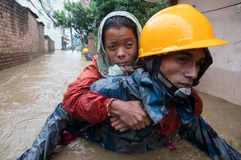 A rescuer carries a woman from a flooded neighbourhood following torrential rain in Kathmandu, Nepal [Narendra Shrestha/EPA]