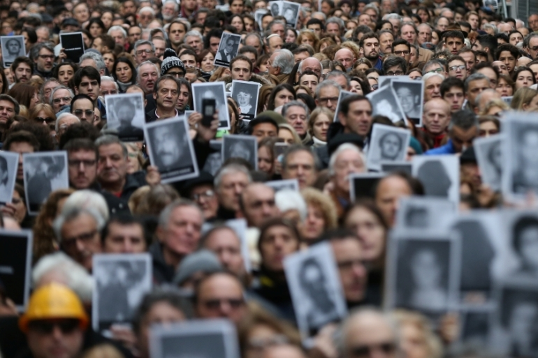 People hold images of the victims of the 1994 bombing of the Argentine Israelite Mutual Association (AMIA) community centre, marking the 25th anniversary of the attack [Agustin Marcarian/Reuters]