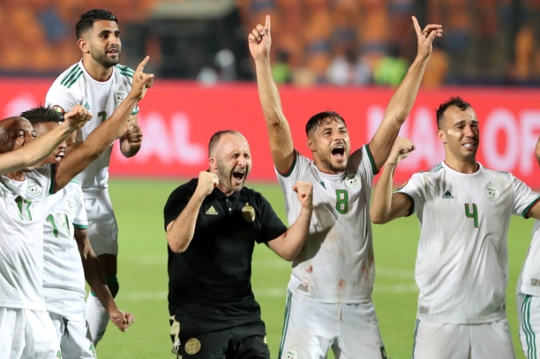 Algeria's Riyad Mahrez, coach Djamel Belmadi and team mates celebrate in front of their fans after winning the final [Suhaib Salem/Reuters]