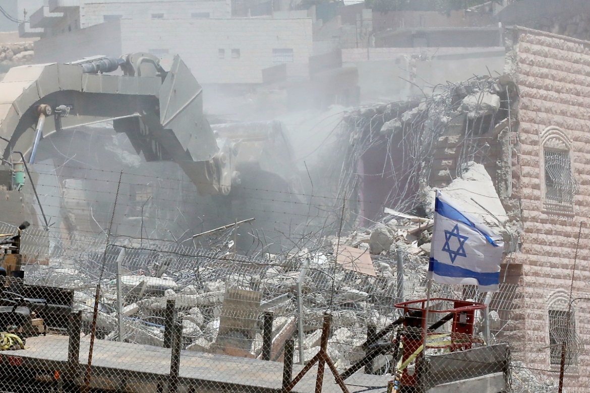 An Israeli flag is seen as security forces tear down one of the Palestinian buildings in the Wadi al-Hummus area. [Hazem Bader/AFP]