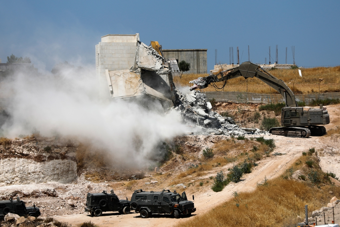 Israeli security forces tear down one of the Palestinian buildings still under construction. [Ahmad Gharabli/AFP]